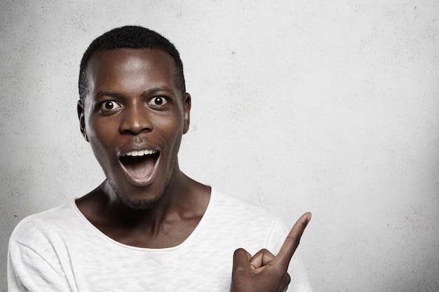 驚いて驚いた表情の白いtシャツを着ているアフリカ人の屋内ポートレート。口を大きく開き、人差し指で空白の壁を示しています。 無料写真