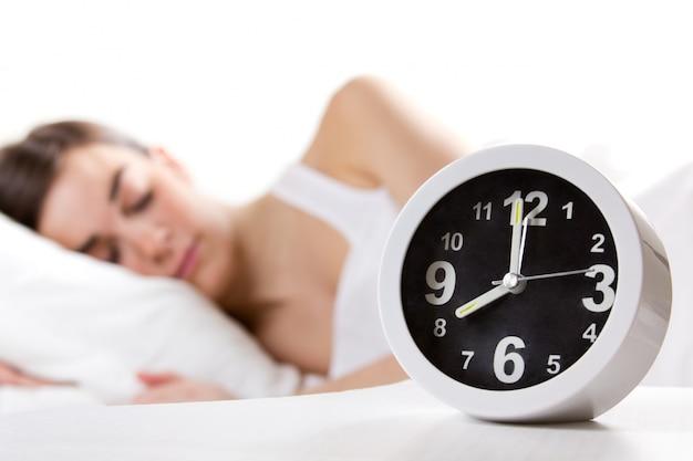 Mulher dormindo ao fundo da imagem, em primeiro plano um relógio analógico apontando as 8h00. (Higiene do Sono)