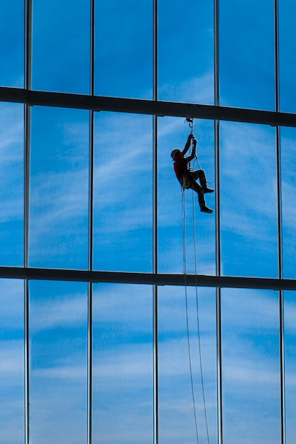 Industrial climber hangs from ropes inside building Premium Photo