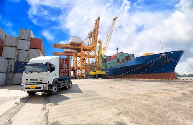 Industrial container cargo freight ship with working crane bridge Premium Photo