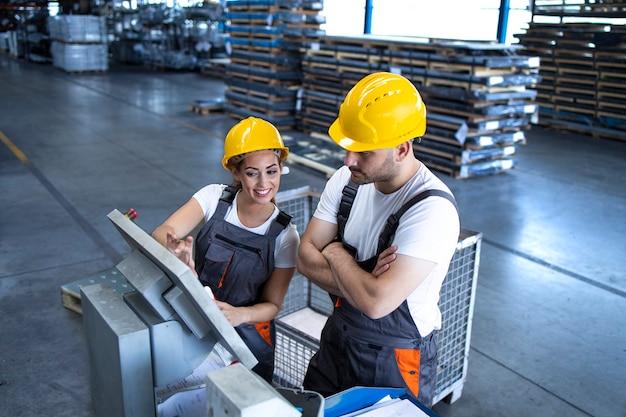 Dipendenti industriali con macchine operatrici hardhat giallo alla linea di produzione utilizzando il nuovo computer software Foto Gratuite