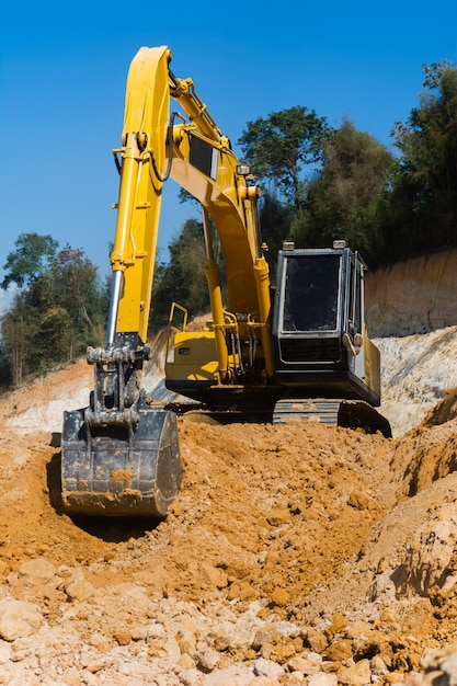 Industrial excavator working on construction site to clear the land of sand and soil Premium Photo