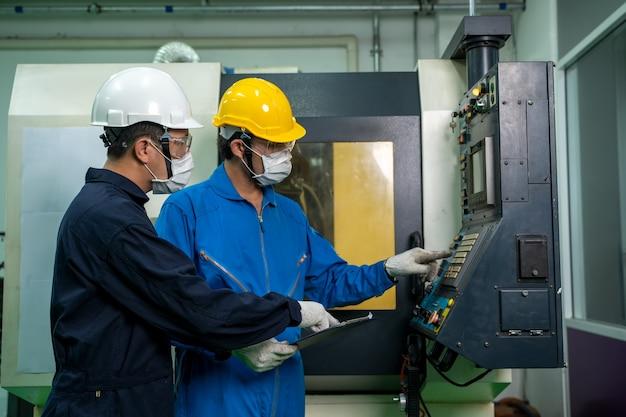 Работник промышленного завода работает и проверяет возле панели электрических счетчиков диспетчерской. Premium Фотографии