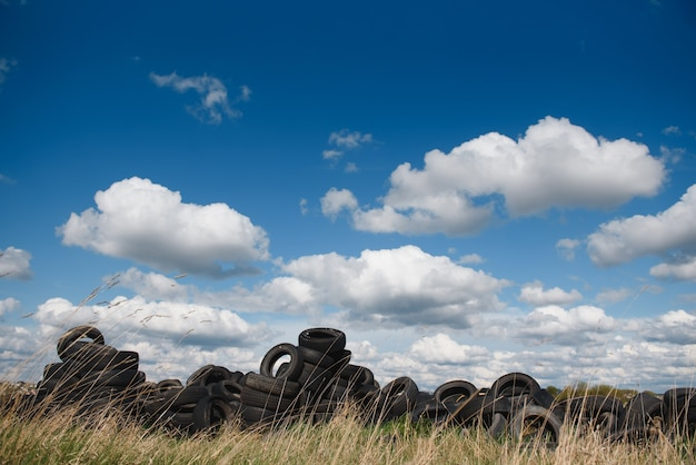 Industrial landfill for the processing of waste tires and rubber tyres. pile of old tires and wheels for rubber recycling Premium Photo