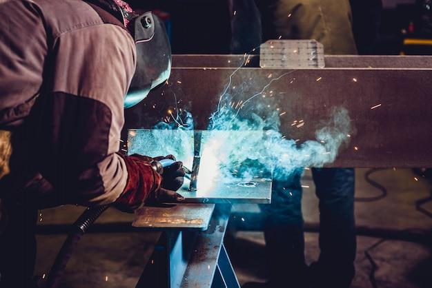 A Welder Welding A Metal Plate