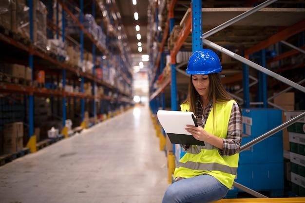 Operaio industriale che controlla l'inventario delle merci nel grande centro di stoccaggio del magazzino e scrive il rapporto sui risultati della distribuzione Foto Gratuite