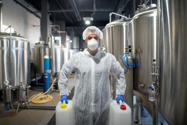 Operaio industriale che tiene lattine di plastica con prodotti chimici nello stabilimento di produzione Foto Gratuite