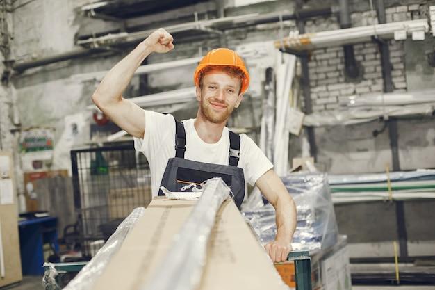 Operaio industriale al chiuso in fabbrica. giovane tecnico con elmetto arancione. Foto Gratuite