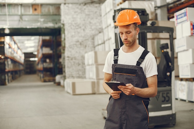 Промышленный рабочий в помещении на заводе. молодой техник в оранжевой каске. Бесплатные Фотографии