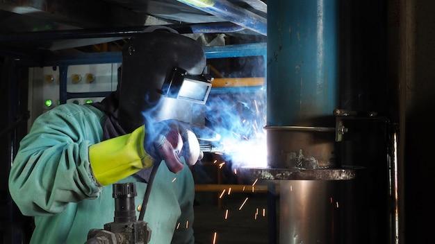 Industrial worker welding steel pipe flange,a spark welding. Premium Photo