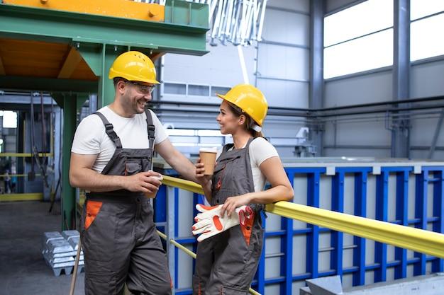 Lavoratori dell'industria in uniforme e attrezzature di sicurezza che si rilassano in una pausa bevendo caffè e parlando all'interno della fabbrica Foto Gratuite