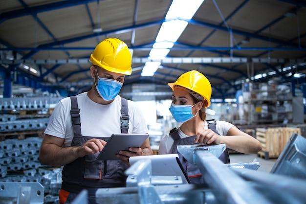 Lavoratori industriali con maschere facciali protette contro il virus corona che discutono sulla produzione in fabbrica Foto Gratuite
