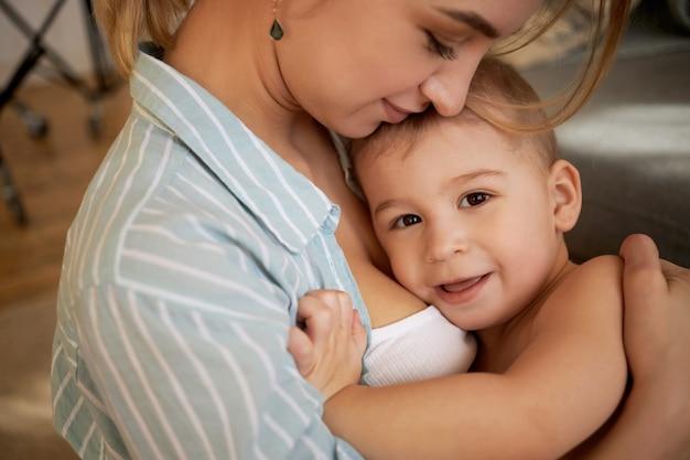 Infanzia, infanzia e maternità. bella giovane madre amorevole che stringe a sé a casa con il suo adorabile figlio adorabile, trascorrendo momenti dolci felici, mostrando amore e affetto, bambino sorridente Foto Gratuite