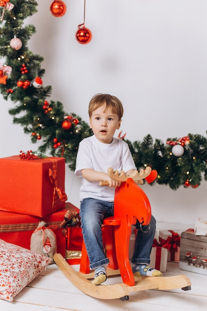Infant baby boy playing at home in christmas evening. holiday decorations, new year eve with colorful lights are on background Premium Photo