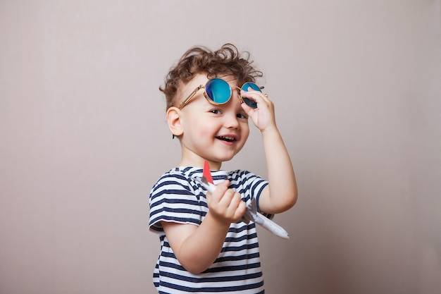 Infant, child with a toy airplane in his hands and sunglasses. tourist Premium Photo