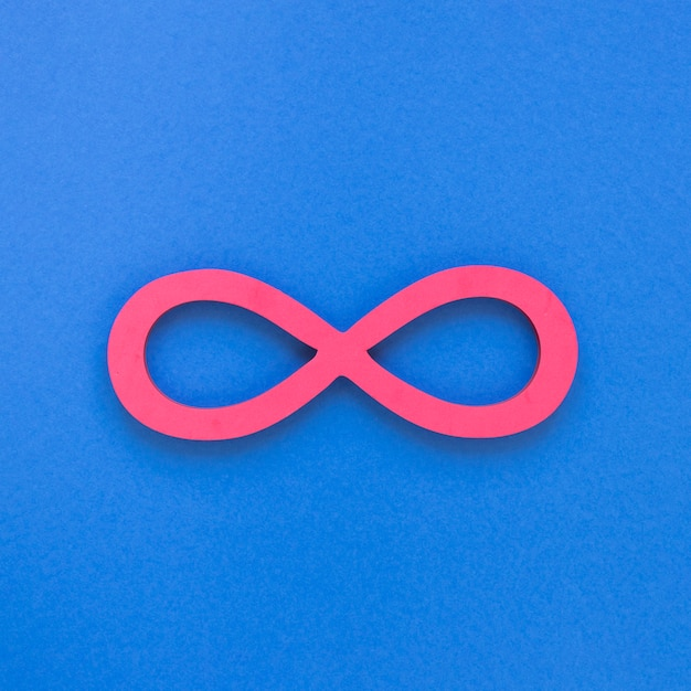 Infinite pink symbol on blue background Free Photo