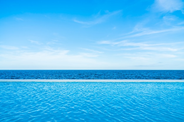 Infinity swimming pool with sea and ocean view on blue sky Free Photo