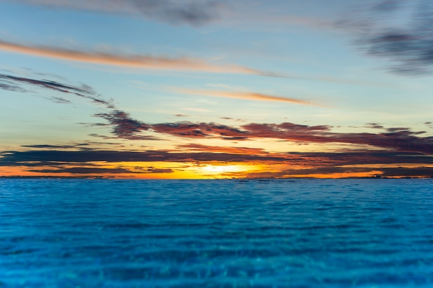 Infinity swimming pool with sunset sky vover the  ocean. Premium Photo