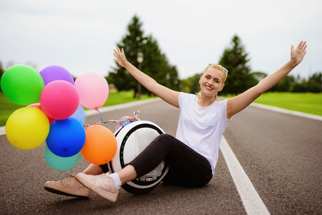Inflatable balls. woman sit with monowheel in road. Premium Photo