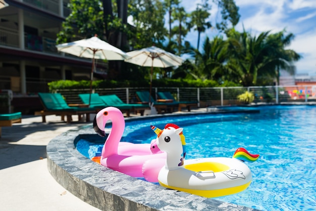 Inflatable colorful white unicorn and pink flamingo at the swim pool. Premium Photo