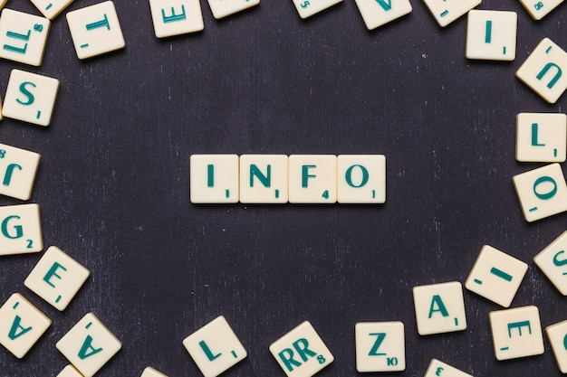 Info scrabble letters arranged over black backdrop Free Photo