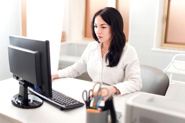 必要な情報。集中して見えるコンピューターで作業している白いローブの暗い髪の医者 Premium写真