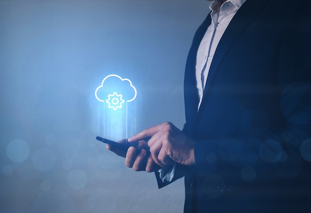 Информационный технолог, держащий телефон со значком облачных вычислений. Premium Фотографии