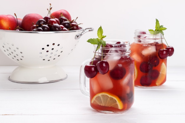 Infused flavored water with cherry, lemon and mint Premium Photo