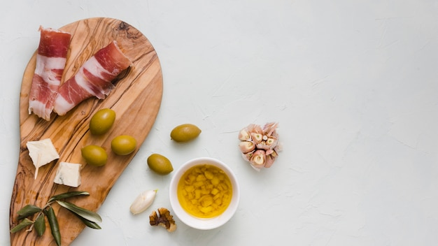 Infused olive oil; olives; garlic club; cheese and bacon isolated on white backdrop Free Photo