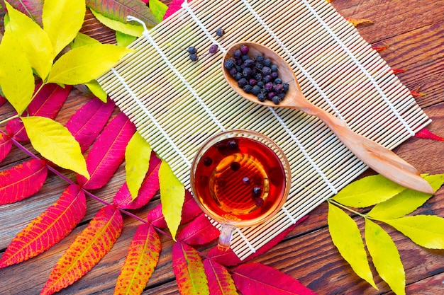 Infusion of hawthorn in a glass bowl, a wooden spoon with dry fruits and bamboo mat Premium Photo