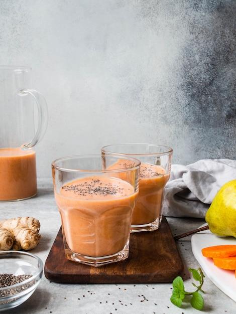新鮮な健康なニンジン、梨、灰色の背景にチア種子と生ingerのスムージーを2杯 Premium写真