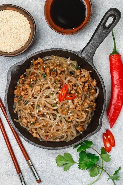 肉醤油、生inger、ごま、コリアンダー、赤唐辛子入りでんぷんガラス麺の中華料理 Premium写真