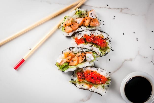 トレンドハイブリッド食品。日本アジア料理。ミニ寿司タコス、サーモンのサンドイッチ、林わかめ、大根、生inger、赤キャビア。白い大理石のテーブル、箸、醤油。コピースペーストップビュー Premium写真