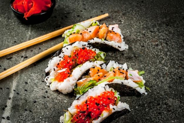 ミニ寿司タコス、サーモンのサンドイッチ、林わかめ、大根、生inger、赤キャビア。 Premium写真