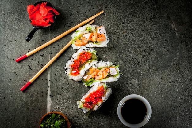 トレンドハイブリッド食品。日本アジア料理。ミニ寿司タコス、サーモンのサンドイッチ、林わかめ、大根、生inger、赤キャビア。黒い石のテーブル、箸、醤油。コピースペーストップビュー Premium写真
