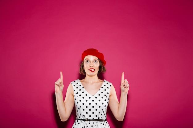 ピンクの上に彼女の唇をかみながら指していると見上げるドレスで興味をそそられる生inger女性 無料写真