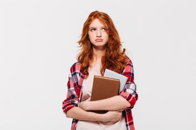 本を押しながらよそ見のシャツで不機嫌な生inger女性 無料写真
