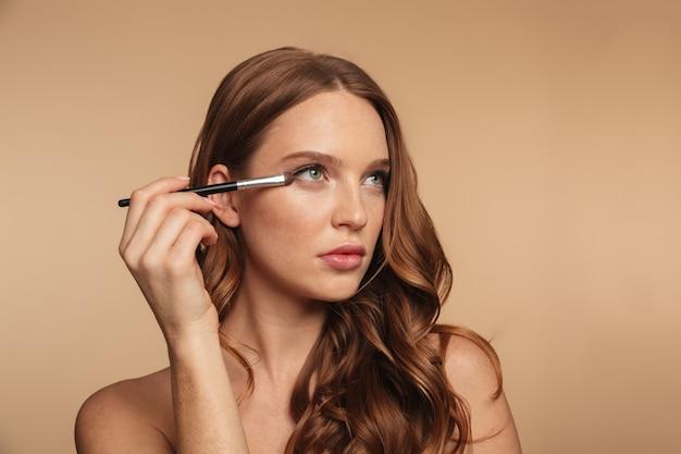 ブラシで化粧品を適用しながらよそ見長い髪の謎の生inger女性の美しさの肖像画 無料写真