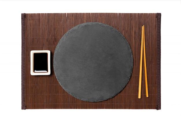 箸と醤油、暗い竹マットに生ingerの空の黒い丸皿 Premium写真