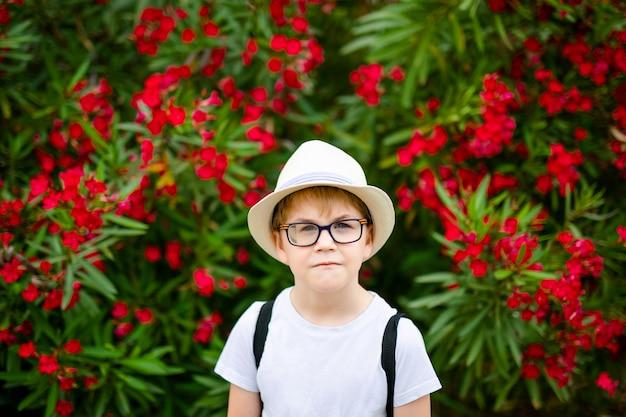 夏の公園で赤い花と緑の茂みの近くの麦わら帽子と大きなメガネで生inger少年 Premium写真