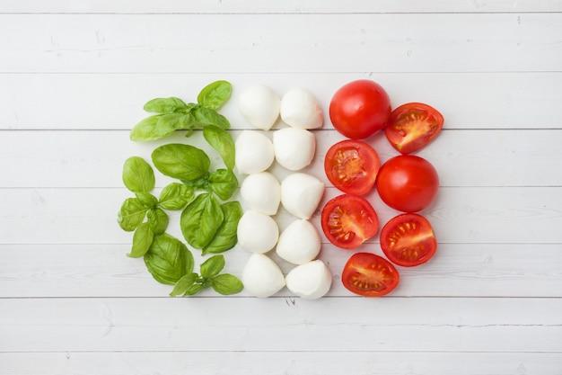 The ingredients for a caprese salad. basil, mozzarella balls and tomatoes. italian flag Premium Photo
