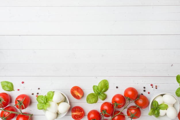 The ingredients for a caprese salad. basil, mozzarella balls and tomatoes Premium Photo