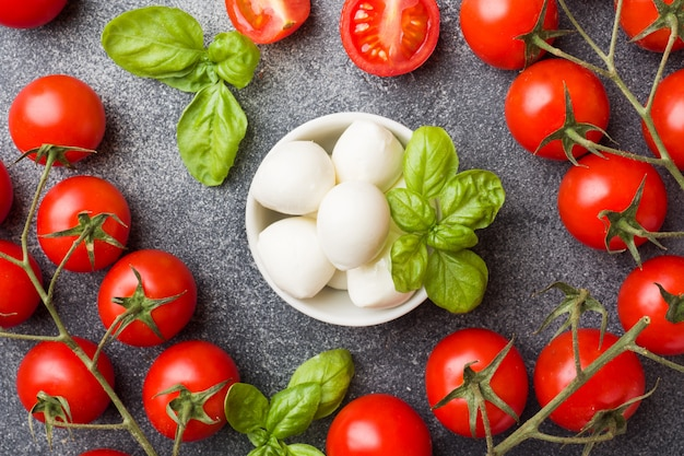 The ingredients for a caprese salad. basil, mozzarella balls and tomatoes. Premium Photo
