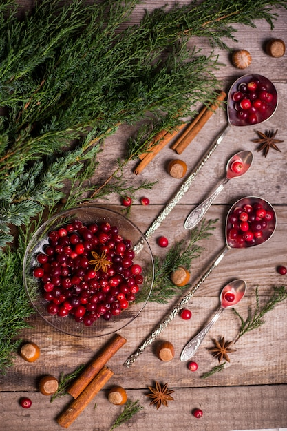 Ingredients for christmas, winter baking cookies. gingerbread, fruitcake, seasonal drinks. cranberries, dried oranges, cinnamon, spices on a wooden table, copy space top view. Premium Photo