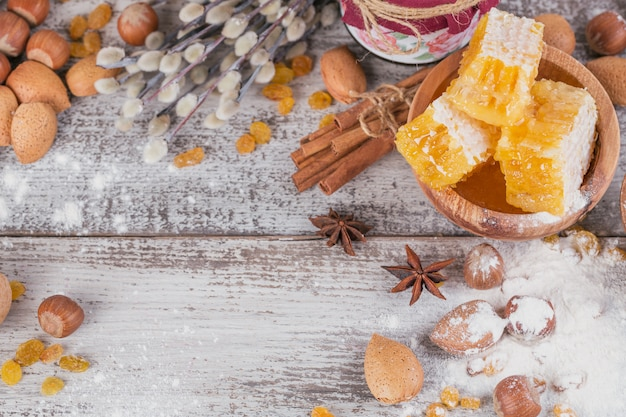 Ingredients for cooking bread or cookies with honeycomb, flour, raisines, mix of nuts, spices Premium Photo