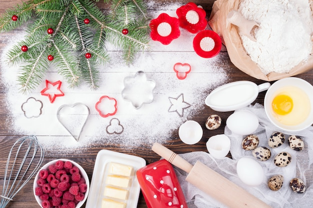 Ingredients for cooking christmas baking with flour, eggs, butter, raspberries milk and kitchen utensils Premium Photo