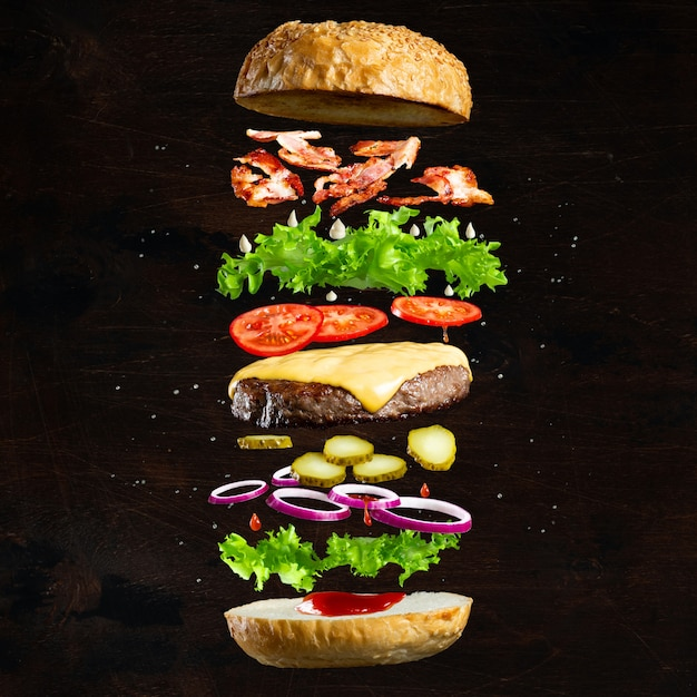 Ingredients of a delicious burger with ground beef patty, lettuce, bacon, onions, tomatoes and cucumbers Premium Photo