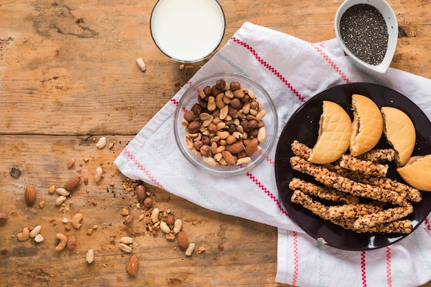 Ingredients; dryfruits; cookies and granola bar on wooden table with napkin Free Photo