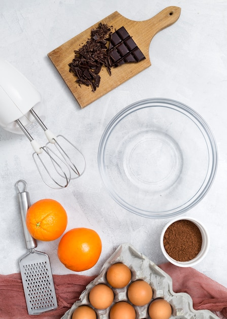 Ingredients; electric mixer; hand grater and empty bowl for preparing the chocolate cake on white surface Free Photo