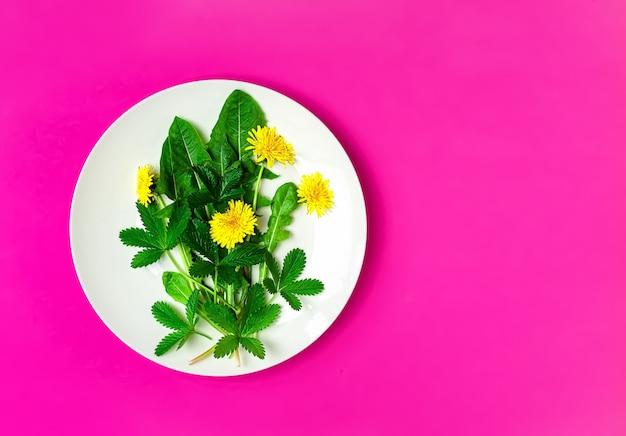 タンポポと食用花を皿に盛り付けた新鮮なグリーンサラダの材料 無料写真